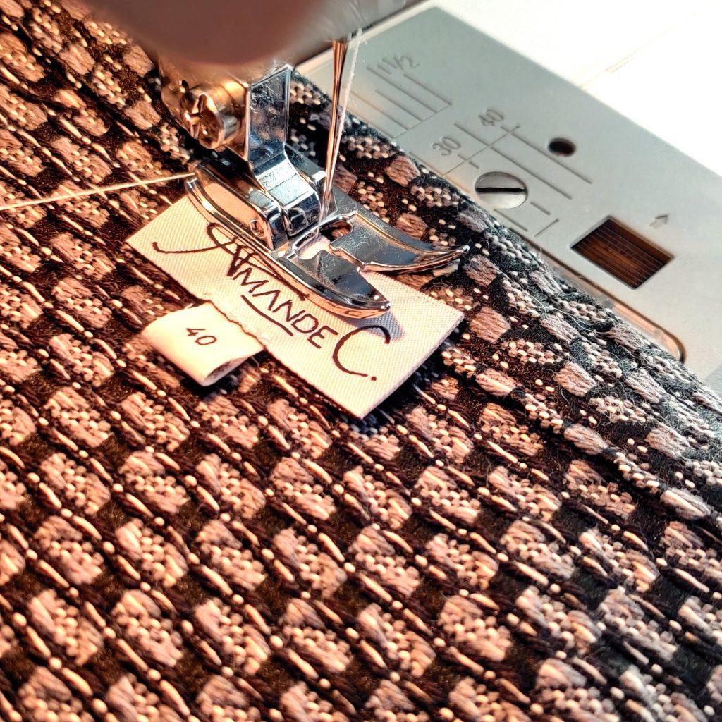 Amande C - création d'un vêtement - pose de la griffe sur le vêtement